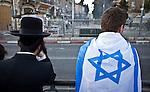 An Ultra Orthodox Jew stands next to a flagged covered Israeli youth as they look at Israeli police officers push away Palestinian protestors outside Damascus gate in Jerusalem Wednesday May 28 2014, during festivities marking Jerusalem day. The Day marks the reunification of Jerusalem following the 1967 Six Day War when Israel captured the Arab part of the city from Jordan. Photo By Eyal Warshavsky