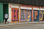 "Middlesex Street East End London E1. Alphabet Street project ""HAPPY"" on shop shutters work by street artist Ben Eine (real name Ben Flynn). Man walking past."