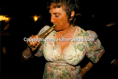 West Bagborough, Somerset. 1997<br /> Tally-ho, she's blowing a hunting horn at the Quantock Staghounds end of season annual hunt ball held at Bagborough House. The competition requires that you blow a variety of Calls; Moving off, Gone to ground and Blowing for home. <br /> The Calls can indicate that the huntsmen and hounds are moving off, and the days hunting begins. There are different Calls to tell The Field exactly what is happening, out front and often out of site. Blowing for Home, blown at the end of the hunting day, is a long, mournful wail and the most complicated call. Some huntsmen have sounded this call in a special & extended way at the end of the season.