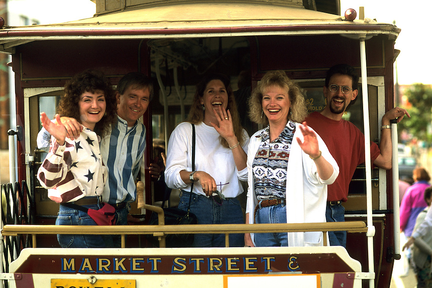 Tourists on nostalgic famous Market Street Cable Car on holiday vacation in San Francisco Californi