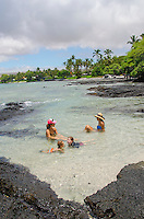 Two local mothers and their children talk and play in a tide pool at a beach in Puako, South Kohala, Big Island.