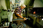 Royal Mews Buckingham Palace London 1990s UK. A blacksmith working at his forge on a horse shoe. 1991