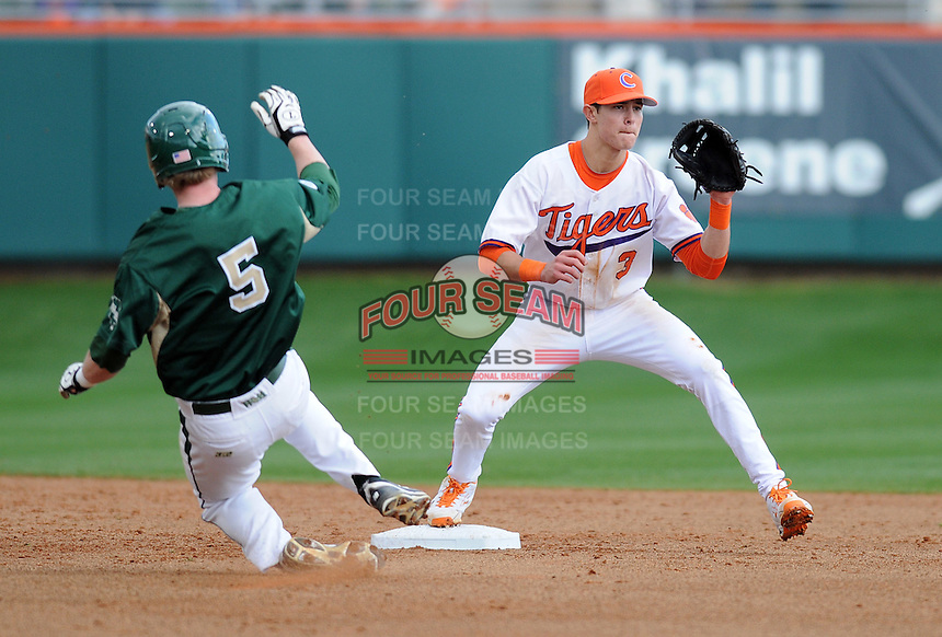 Shortstop Tyler Krieger (3) of the Clemson Tigers waits for the throw as he attempts to put out Ryan Lindemuth (5) of the William & Mary Tribe on Opening Day, Friday, February 15, 2013, at Doug Kingsmore Stadium in Clemson, South Carolina. Clemson won, 2-0. (Tom Priddy/Four Seam Images)