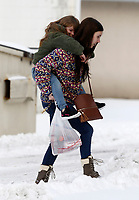 Brynlee (cq) Gray, 6, gets a piggyback ride Thursday, February 18, 2021, from her mom Taylor to avoid getting her tennis shoes wet as they return from the store on an errand in Fayetteville. The National Weather Service forecast for Friday is mostly sunny skies with a high near 37 degrees. Check out nwaonline.com/210219Daily/ and nwadg.com/photos for a photo gallery.<br /> (NWA Democrat-Gazette/David Gottschalk)