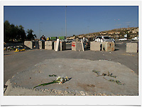 Palestinians gather at concrete blocks at the exit of the Palestinian village of Beit Sira to Road No. 443. Road 443 is one of the main throughways of the West Bank. Its overall length is 25.5 KM, 14 out of which run through the heart of the West Bank. .With the break of the second Intifada at the end of 2000, Israel had severely restricted Palestinian movement on road 443, which was their main road from the Beit Sira, Saffa, Beit Liqiya, Kharbatha al-Misbah, Beit Ur al-Tahata, Beit Ur al-Foqqa and al-Tira villages to Ramallah. These restrictions were harshened in 2002, when Palestinian movement was completely prohibited. In recent years all entries and exits from the road to the area's villages were blocked with gates and concrete slabs. Photo by Quique Kierszenbaum