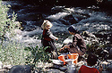 Iraq 1985  Kurdish little girl with her mother washing dishes in a river on their way to exile  Irak 1985 Sur la route de l'exil, petite fille kurde avec sa mere  lavant la vaisselle dans une riviere