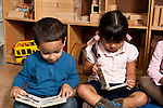 Education preschool 3-4 year olds boy and girl sitting side by side both looking at board books