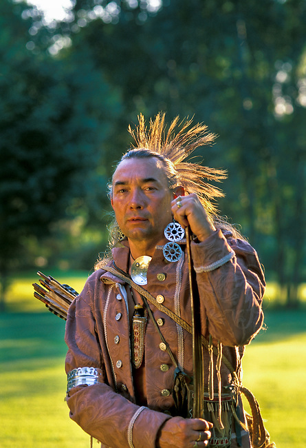 Late 1700's Shawnee warrior re-enactor, Roger Moore, dressed in traditional Shawnee clothing holds a traditional wooden bow and quiver with arrows that would have been used for hunting and warfare. Surroundings are the wooded homelands of the Shawnee Indians in central Ohio. Model released