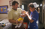 Staff nurse in blue, Alder Hey Hospital Manchester NHS Childrens Ward baby and father. 1980s 1988
