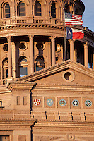 Close up of the Texas Capitol Dome with US stars and strips and Texas Lone Star Flags waving in the wind symbolizing Texas patriotism and valor of the Republic of Texas.