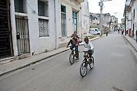Street scene Havana Cuba. 13-12-10 Boys cycle down a residential street.