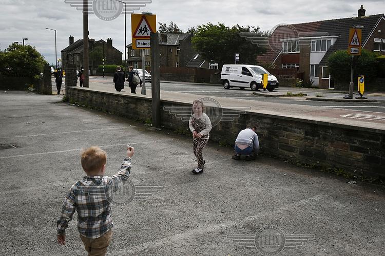 Irish Traveller children play in the car park of a derelict pub as local children walk past on their way to school.