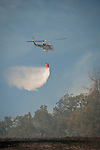 Cal Fire and local government crews from East Bay MUD and Moke Hill, along with airtankers and helicopters fight an 60 acre wildland fire near the Middle Bar Bridge over the Mokelumne River, Calaveras County, Calif...CalFire's Helicopter 404 (Bell EH-1X) drops Pardee Reservoir water on fire hotspots.