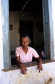 Bahia State, Brazil. Elderly woman looking out from the window.