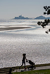 Swansea, UK, 25th March 2020.<br />A mother runs with her pram as people get their hit of daily excercise during the Coronavirus lockdown in the stunning spring weather at Mumbles near Swansea this afternoon.