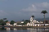 Paraty, Rio de Janeiro, Brazil. Colonial seaside port town with baroque church of Santa Rita and a wooden launch.