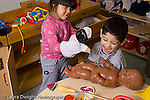 Preschool 3-4 year olds  boy and girl interacting and playing together wearing dressup clothes horizontal playing with puppet