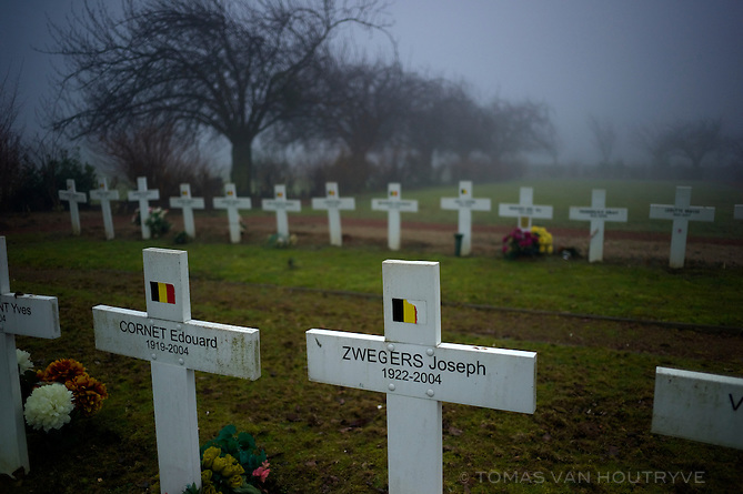 Soldier's graves are seen in the fog in the Schaerbeek Cemetery on the edge of Brussels and Zaventem, Belgium on Feb. 17, 2013. The cemetery is split by the border between Dutch-speaking Flanders and Brussels, which has  a bilingual French-speaking majority. Many of the Belgian flags on the soldiers' headstones have been defaced. Language inequalities between officers and foot soldiers during WWI is an often repeated sore point in the Belgian language dispute.