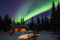 Northern lights over a rustic log cabin in the Alaska Range mountains, Interior, Alaska.