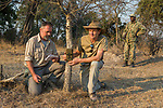 African Lion (Panthera leo) biologists, Luke Hunter and Jake Overton, placing camera trap on tree with park scout, Timbo Frackson, keeping watch, Kafue National Park, Zambia