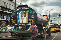 """Nigeria. Enugu State. Enugu. Town center. Traffic stopped at red light. A truck is carrying clean water supply. The tank is covered with religious precepts ( Holy Spirit is my power. To God be the glory) and a drawing with Jesus Christ (I drank this cup for your sake). An Igbo man works as a street seller and walks in the middle of the cars. He carries a cardboard box in his arms with sweets to be sold. Two yellow auto rickshaw used by """"Keke"""" drivers for transporting people around town. The  tricycle better known in Nigeria as the Keke NAPEP is gaining the dominance on Nigerian roads sweeping every street of cities and villages. The auto rickshaw is a common form of urban transport, both as a vehicle for hire and for private use. Enugu is the capital of Enugu State, located in southeastern Nigeria. 5.07.19 © 2019 Didier Ruef"""