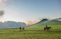 At sunset, visitors enjoy horseback riding over the mystical hills of Kohala, Hawai'i Island. This part of Kohala is in Waimea, near sunset.