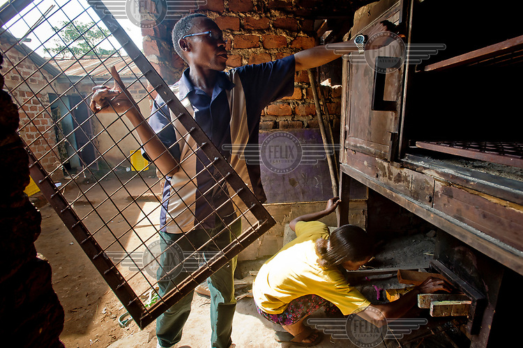 In the Kawempe district of Kampala, Pastor David Kyambadde, director of the Frontier Orphanage and Elderly Home (FOEH) group, puts the shelves into an economical combustion oven while a woman fill it with firewood. The oven uses a small amount of wood to produce maximum cooking capacity, allowing significant savings. Thanks to the acquisition of the oven, FOEH undertook a bakery business to generate income improving the lives of its members.