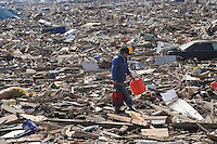 A man carries a can of fuel amongst the splintered remains of houses in the  town of Natori, after the Tsunami devastated the entire pacifc coastline of Japan after the earthquake and tsunami devastated the area Sendai, Japan.<br />