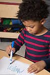 Education preschool 4 year olds boy writing letters of his name with marker