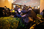 "DC police push anti-Trump demonstrators over a bush in front of the Capital Hilton during the ""Million MAGA March"" on November 14, 2020 in Washington, D.C.  Thousands of supporters of U.S. President Donald Trump gathered to protest the results of the 2020 presidential election won by President-Elect Joe Biden.  Photograph by Michael Nagle"