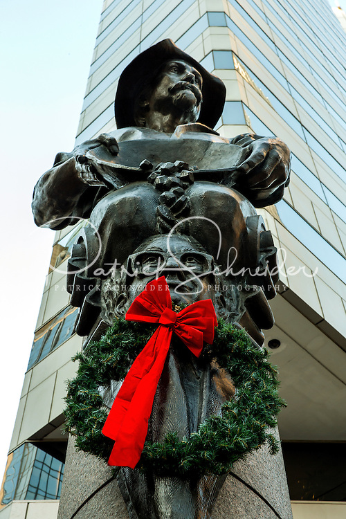 Photography of  Charlotte area Christmas time scenes.<br /> <br /> A christmas wreath adds a little color to the panning for gold statue, this is one of four statues at the corner of Trade and Tryon Streets in uptown Charlotte, North Carolina,.. This one represents commerce.<br /> <br /> Charlotte Photographer - PatrickSchneiderPhoto.com