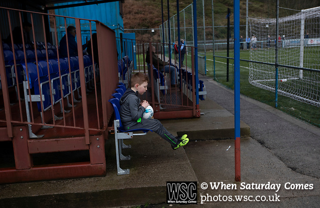 A young fans seated behind the goal during the second-half as Cambrian and Clydach Vale (in blue) take on Cwmbran Celtic at King George's New Field in a Welsh League Division One match, the top division of the Welsh Football League and the second level of the Welsh football league system. The club, formed in 1965 reached the final of the 2018-19 League Cup final and can count on ex-England manager Terry Venables as a former club chairman. Cambrian and Clydach Vale won this match 2-0, watch by a crowd of around 100 spectators.