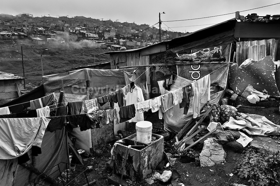Washed clothes hung out to dry in the backyard of a wooden shack, a home of the internally displaced family, slum of Ciudad Bolívar, Bogota, Colombia, 26 May 2010. With nearly fifty years of armed conflict, Colombia has the highest number of civil war refugees in the world. During the last ten years of the civil war more than 3 million people have been forced to abandon their lands and to leave their homes due to the violence. Internally displaced people (IDPs) come from remote rural areas, where most of the clashes between leftist guerrillas FARC-ELN, right-wing paramilitary groups and government forces takes place. Displaced persons flee in a hurry, carrying just personal belongings, and thus they inevitably end up in large slums of the big cities, with no hope for the future.