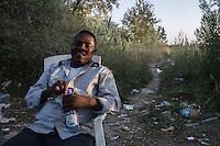 accampamento di migranti a Subotiza, nei pressi della vecchia fabbrica  camp for migrants in Subotiza , near the old factory  un migrante seduto con una bottiglia di acqua