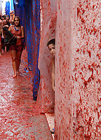 BUNYOL, SPAIN - AUGUST 31: A boy observe behind a plastic wich protect the houses during the Tomatina August 31, 2005 in Bunyol, Valencia, Spain. Approximately 45,000 people pelted each other with a little over 100.000 kilograms of tomatoes. The tomatina is known as the world's largest tomato battle. Photo by Ander Gillenea