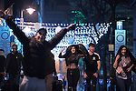 """© Joel Goodman - 07973 332324 . 16/12/2016 . Manchester , UK . People use jackets to shelter from rain , on Canal Street in Manchester's Gay Village . Revellers out in Manchester City Centre overnight during """" Mad Friday """" , named for being one of the busiest nights of the year for the emergency services in the UK . Photo credit : Joel Goodman"""