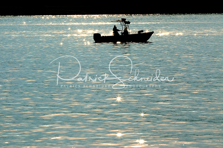 """Event photography of the Charlotte Symphony performing in a free outdoor concert June 17, 2012 at Duke Energy's McGuire Nuclear Station EnergyExplorium in Cornelius, NC. The symphony orchestra performed a """"musical travels"""" program. Boaters on Lake Norman enjoy the music while floating on the water nearby."""