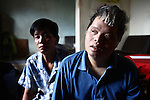 """Dang Chi Tam, 42, a second generation victim of Agent Orange, sits with her brother Dang Chi Trung, 43, in their home in Da Nang, Vietnam. Their parents, now deceased, were long-time members of the Communist Party, and served in the wars against the French and Americans. Trung is the sole caregiver for his sister, who is mentally disabled and unable to speak or care for herself. """"Even personal hygiene she doesn't know how to do,"""" he says. """"Even to go to the toilet, she doesn't know how to do."""" They survive on about $60 a month that is provided by the Vietnamese government. """"It is very difficult for us to live,"""" he says. """"Because I have to care for her, I cannot go out for very long. It is very difficult for me to get a job."""" The Vietnam Red Cross estimates that 3 million Vietnamese suffer from illnesses related to dioxin exposure, including at least 150,000 people born with severe birth defects since the end of the war. The U.S. government is paying to clean up dioxin-contaminated soil at the Da Nang airport, which served as a major U.S. base during the conflict. But the U.S. government still denies that dioxin is to blame for widespread health problems in Vietnam and has never provided any money specifically to help the country's Agent Orange victims. May 29, 2012."""