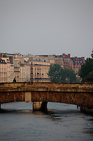 A view of a bridge onto the Seine river, from the Ile de la Cité in Paris, with a person, in the sunrise light. There are some trees and the typical buildings of the Rive Gauche on the background.<br /> <br /> You can download this file for (E&PU) only, but you can find in the collection the same one available instead for (Adv).