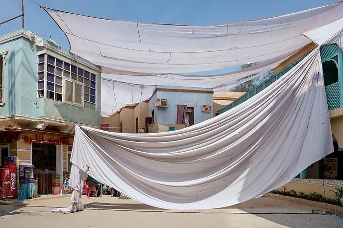 """Shooting the series """"Al Halal"""", Egypt Mars 2017 (Cedar Group). Very popular in Egypt, the style of series """"shaabi"""" (from the people) takes place in poor areas. In a society where social classes are sharply divided, television has to be for everyone. On this shoot, the studio replicates a quarter of Cairo. This sheet is mounted to be used to filters the sunlight.<br /> <br /> Tournage de la série """"Al Halal"""", Egypte Mars 2017 (Cedar Group). Les Egyptiens sont friands des séries de style """"shaabi"""" (populaires), dont les histoires se déroulent dans des quartiers pauvres. Dans une société où les différentes classes sociales sont imperméables les unes aux autres, la télévision doit plaire à tous. Sur ce tournage, le studio réplique un quartier du Caire. Le voile qui permet de filtrer la lumière du soleil est en train d'être monté."""