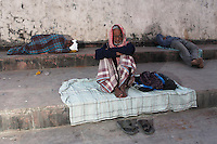 Men sit and sleep on the steps along the banks of the Ganges River in Kolkata, India. November, 2013