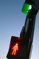Pedestrian symbol on a traffic light turns red to warn pedestrians on a road crossing, Paris, France.