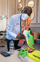 Eliud Kipchoge (KEN) signs his autograph on a pair of running trainers after the virtual and socially distanced press conference from inside the official hotel [location not disclosed] and biosecure bubble for the historic elite-only 2020 Virgin Money London Marathon on Sunday 4 October. The 40th Race will take place on a closed-loop circuit around St James's Park in central London. Wednesday 30th September 2020. Photo: Bob Martin for London Marathon Events<br /> <br /> For further information: media@londonmarathonevents.co.uk