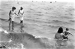 Southend on Sea Essex. Mother and child, two senior women paddling. 1970