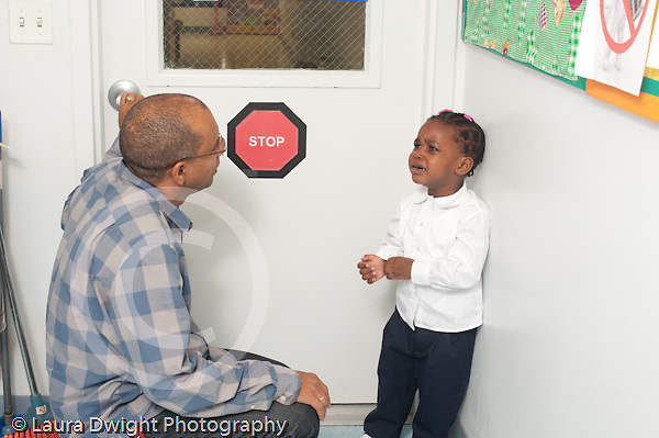 Education preschool 2-3 year olds start of year male teacher talking to sad girl who wants to leave classroom