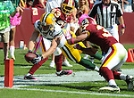 Green Bay Packers receiver Jordy Nelson, center, takes the ball to the one-yard-line early in the second quarter between Washington Redskins DeAngelo Hall (23) and Reed Doughty (37) at FedEx Field in Landover, Md., on Oct. 10, 2010.  The Packers failed to score a touchdown on the series.