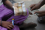 Alamgir and his friend with pieces of cloth with industrial adhesive dendrite which is used as a sniifing addiction by Indian street children. Alamgir is staying here for last 6 years from the time he ran away from his home due to domestic violence and poverty. As per his version his father was a drunkard and used to beat his mother for no reason. His father even could not earn enough money to buy food for their big family. Due to this traumatic situation he ran away from house at the age of seven. Ever since, the Sealdah railway station in Kolkata has been his home. As far as company is concerned, he had not much reason to miss his family. There are around 500 children, from 5 to 16 years, who live in the premises of Kolkata's second largest train terminus. Most of them addicted to Brown Sugar and sniffing industrial adhesive Dendrite. They say they don't feel hungry if they take the drugs. Their presence is conspicuous, even in a place that registers an average footfall of 1.4 million on weekdays. Their activities cover a wide range, from begging, to pulling handcarts, to petty theft, to selling odds and ends on the platform or on trains. The money, earned or ill-gotten as the case may be, is spent in procuring heroin, brown sugar, cocaine, and tubes of Dendrite. Calcutta, West Bengal, India. Arindam Mukherjee