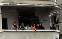 "Palestinians looking from there a damaged balcony,  after isreal withdrawal from gaza strip.March.03.2008.""phto by Fady Adwan"""