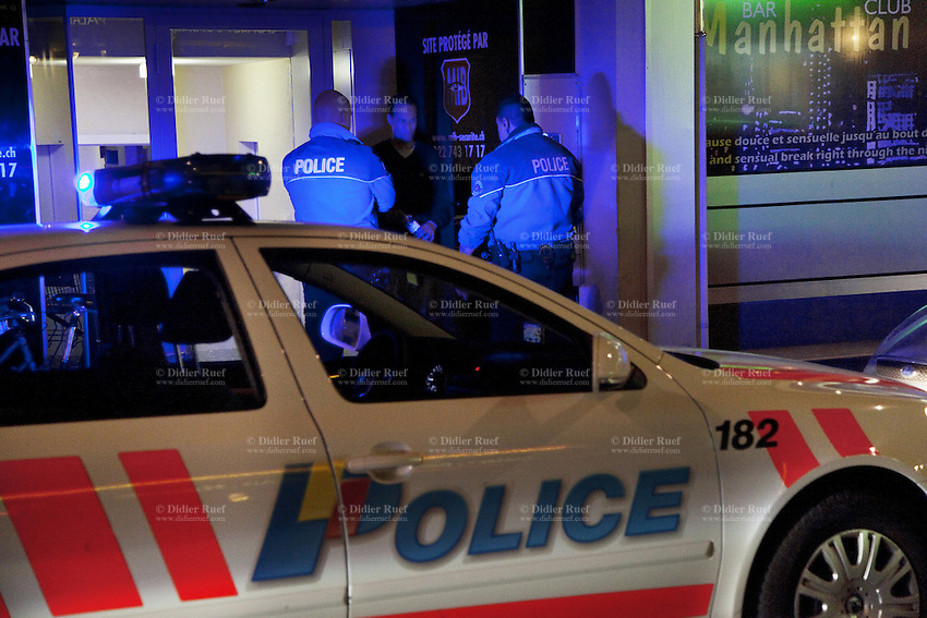 """Switzerland. Geneva. Two police officers arrest a man on the Berne street in the heart of the Paquis neighborhood, known for its nightlife and Red-light district. The policemen have stopped the man while driving under the influence of alcohol. Driving under the influence (DUI), drunken driving, drunk driving, drink driving, operating under the influence, drinking and driving, or impaired driving is the act of driving a motor vehicle with blood levels of alcohol in excess of a legal limit (""""Blood Alcohol Content"""", or """"BAC""""). Both policemen are wearing a ballistic vest, bulletproof vest or bullet-resistant vest which is an item of personal armor that helps absorb the impact from knives, firearm-fired projectiles and shrapnel from explosions, and is worn on the torso. Soft vests are made from many layers of woven or laminated fibers and can be capable of protecting the wearer from small-caliber handgun and shotgun projectiles. 01.04.12 © 2012 Didier Ruef"""