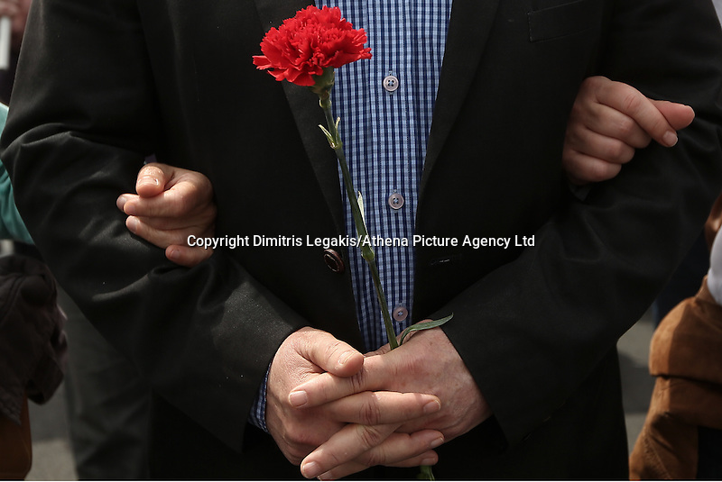 Pictured: Panayiotis Lafazanis of Laiki Enotita party holding a red carnatio, joins other left wing party supporters Sunday 08 May 2016<br /> Re: Members of left wing parties gather outside the Greek Parliament, while MPs vote on pension and welfare reforms, Athens, Greece